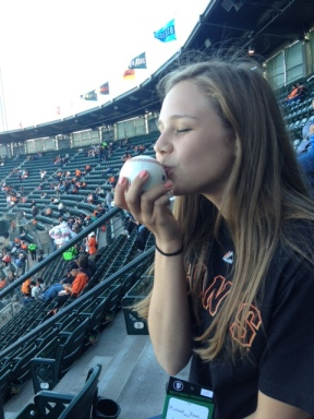 Marisa Anz, a budding broadcaster and member of the Zephyr news team, kisses a baseball she received from a Giants player during the San Francisco Giants vs. Cincinnati Reds game during NBTB 2012.